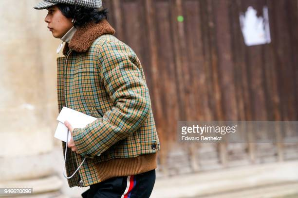 A guest wears a checked coat with brown fur outside Thom Browne during Paris Fashion Week Menswear Fall Winter 20182019 on January 20 2018 in Paris...