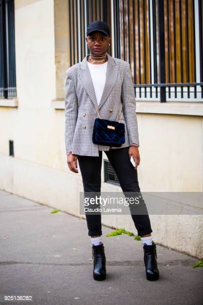 A guest wears a checked jacket black baseball hat and black hells boots on the streets of Paris after the Dior show during Paris Fashion Week...