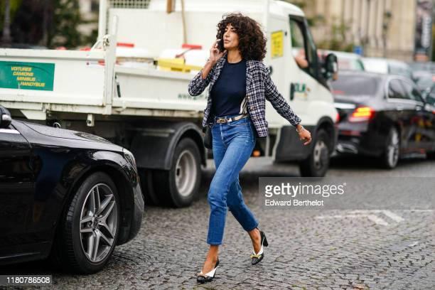 Guest wears a checked pattern jacket, a navy blue top, a belt, blue denim pants, black shoes, outside Chanel, during Paris Fashion Week - Womenswear...
