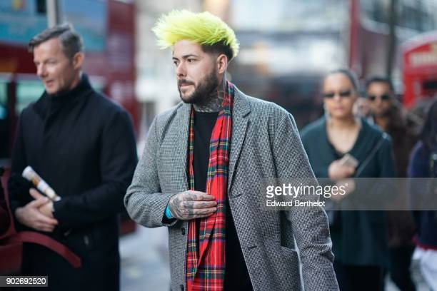 A guest wears a checked red scarf a gray jacket has yellow hair during London Fashion Week Men's January 2018 at on January 7 2018 in London England