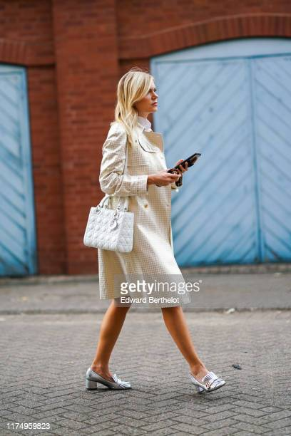 Guest wears a checked trench coat, a white shirt, a Lady Dior white quilted bag, Gucci silver shoes, during London Fashion Week September 2019 on...