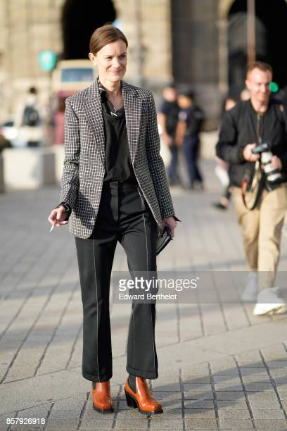 A guest wears a checkered blazer jacket a black top black flare pants brown leather shoes outside Louis Vuitton during Paris Fashion Week Womenswear...