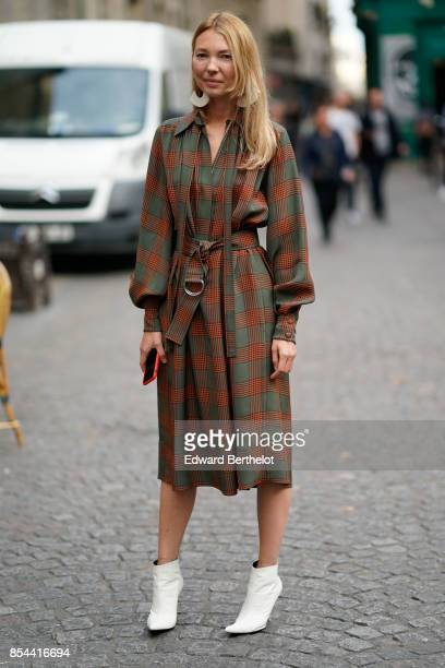 A guest wears a checkered dress white shoes outside Koche during Paris Fashion Week Womenswear Spring/Summer 2018 on September 26 2017 in Paris France