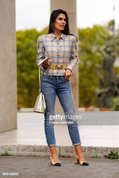 A guest wears a checkered jacket blue jeans chanel slingbacks shoes a bag outside Valentin Yudashkin during Paris Fashion Week Womenswear...