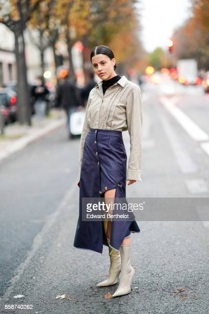 A guest wears a checkered shirt a blue skirt gray boots outside John Galliano during Paris Fashion Week Womenswear Spring/Summer 2018 on October 1...