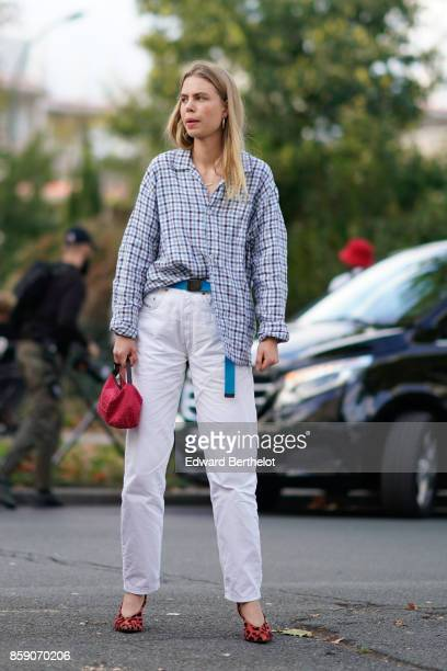 A guest wears a checkered shirt white pants a red bag red shoes outside CDG Comme des Garcons during Paris Fashion Week Womenswear Spring/Summer 2018...
