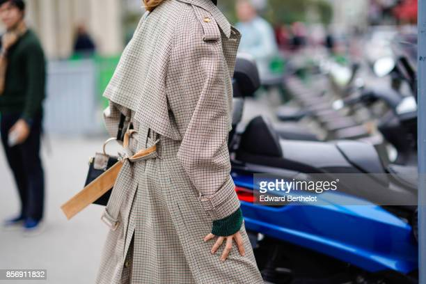 A guest wears a checkered trench coat a black top sportswear red pants outside Giambattista Valli during Paris Fashion Week Womenswear Spring/Summer...