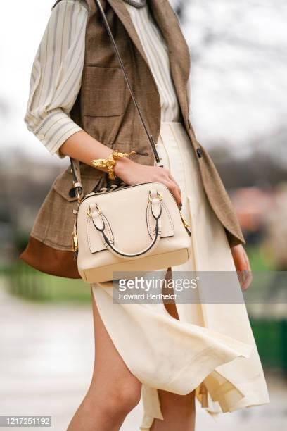 Guest wears a Chloe bag, a golden bracelet, a brown jacket, outside Chloe, during Paris Fashion Week - Womenswear Fall/Winter 2020/2021, on February...
