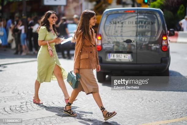 A guest wears a Christian Dior tancolor suede jacket a green Christian Dior bag light camel bermuda shorts black gladiator espadrilles outside Dior...