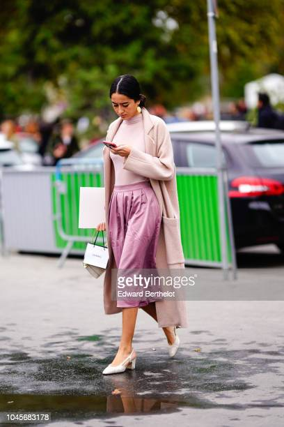 A guest wears a coat a pink skirt a white turtleneck white shoes outside Chanel during Paris Fashion Week Womenswear Spring/Summer 2019 on October 2...