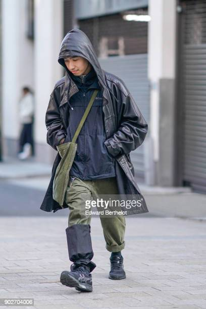 A guest wears a coat with a hood a green bag green khaki pants black boots during London Fashion Week Men's January 2018 at on January 7 2018 in...