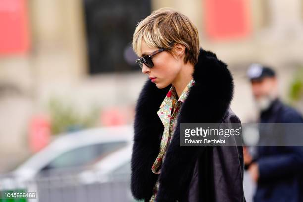 A guest wears a coat with black fur sunglasses outside Chanel during Paris Fashion Week Womenswear Spring/Summer 2019 on October 2 2018 in Paris...