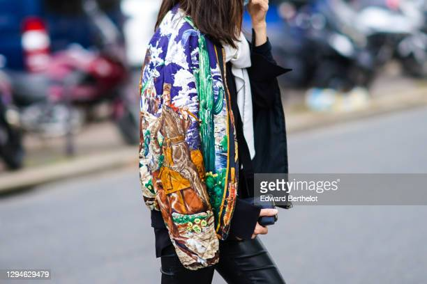 Guest wears a colored bomber jacket with printed colored sky clouds and drawings, outside Hermes, during Paris Fashion Week - Womenswear Spring...