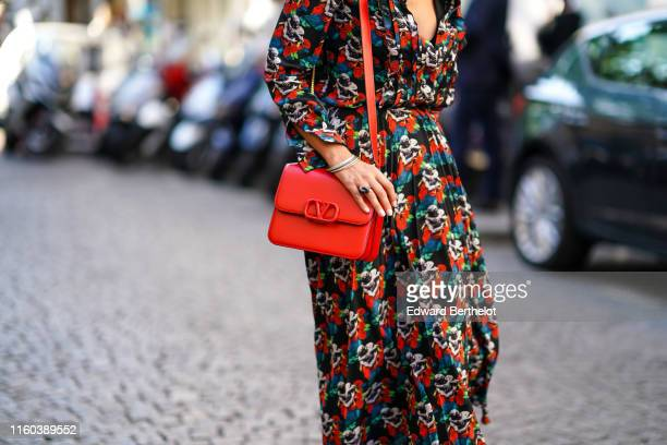 Guest wears a colored floral print dress, a red Valentino bag, outside Valentino, during Paris Fashion Week -Haute Couture Fall/Winter 2019/2020, on...