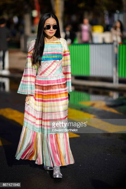 A guest wears a colored striped dress pleated outside Chanel during Paris Fashion Week Womenswear Spring/Summer 2018 on October 3 2017 in Paris France