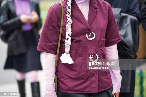 A guest wears a colorful fabric braid a mauve hineck tulle top with glittering tiny silver dots a plumcolor short sleeves jacket with large pockets...