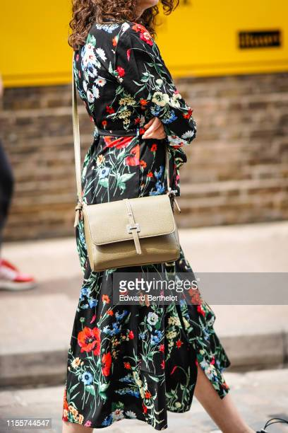 A guest wears a colorful floral print black flowing dress a beige bag during London Fashion Week Men's June 2019 on June 09 2019 in London England