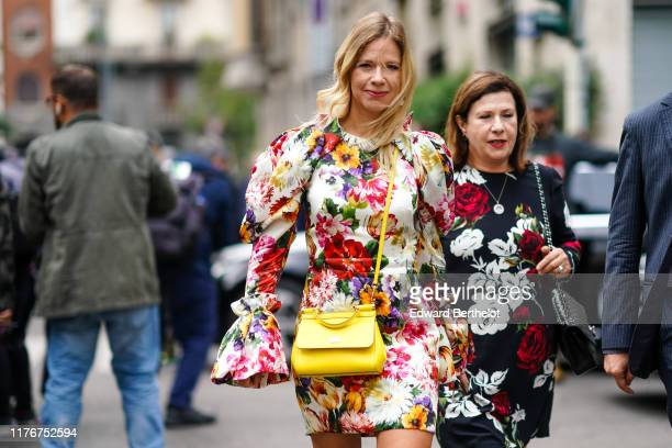 Guest wears a colorful flowers print mini dress with puff sleeves and circular cuffs, a yellow bag ; A guest wears a white and red roses print black...