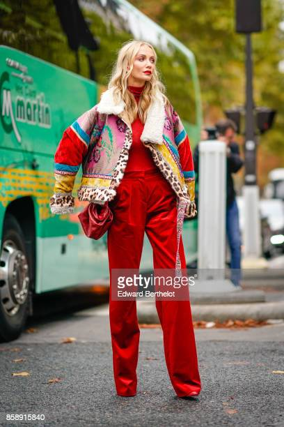 A guest wears a coloruful coat red pants outside Valentino during Paris Fashion Week Womenswear Spring/Summer 2018 on October 1 2017 in Paris France