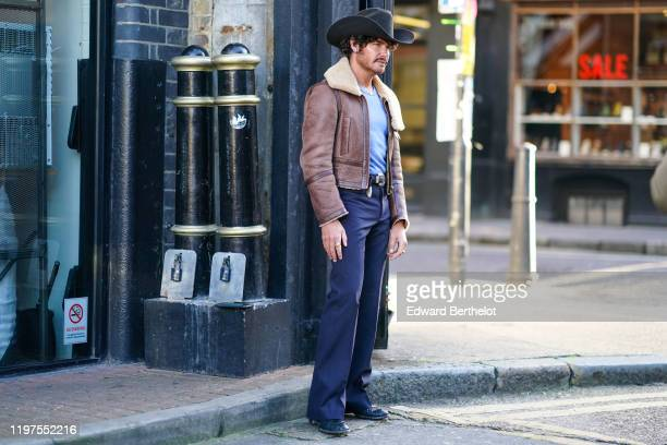 A guest wears a cowboy hat a brown leather aviator jacket with sheep wool inner lining a blue tshirt a belt with metallic buckle blue flare pants...