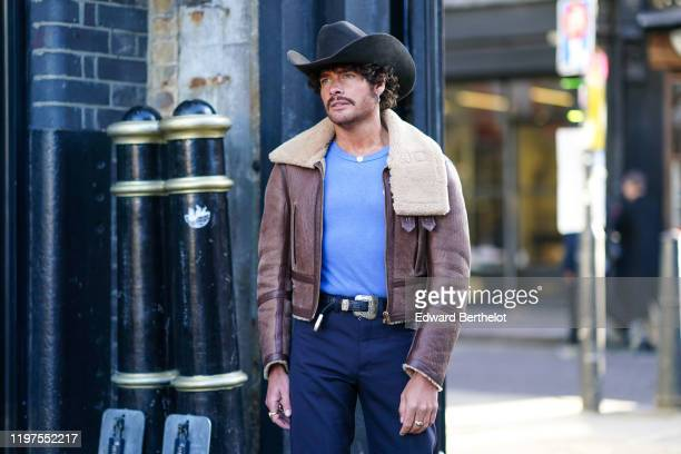 A guest wears a cowboy hat a brown leather aviator jacket with sheep wool inner lining a blue tshirt a belt with metallic buckle blue pants a...