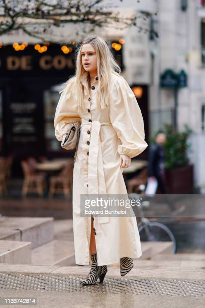 A guest wears a cream color long dress with puff sleeves a beige quilted bag beige zebra pattern ankle boots during Paris Fashion Week Womenswear...