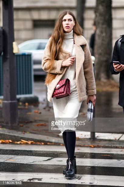Guest wears a cream-color hi-neck dress, an aviator jacket with sheep wool inner lining, black leggings, black leather shoes, a red bag, outside Miu...