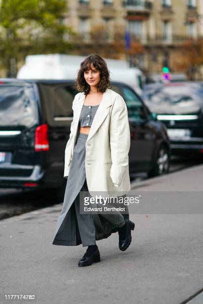 Guest wears a cream-color leather oversized jacket, a grey crop top, a long grey wrap-skirt, black boots, outside Rochas, during Paris Fashion Week -...