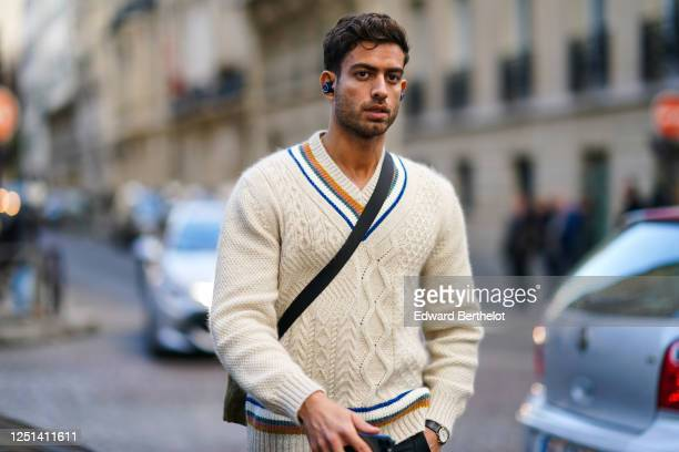 Guest wears a cream-color V-neck sweater, during Paris Fashion Week - Menswear F/W 2020-2021 on January 17, 2020 in Paris, France.