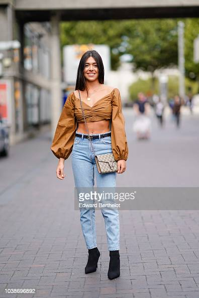 b1cc16ba5 A guest wears a cropped bare belly top, a Gucci bag, blue denim... News  Photo - Getty Images