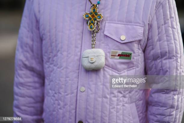Guest wears a cross-shaped bejeweled necklace, a Chanel-Apple Airpods case, an Egonlab pale purple padded jacket, outside Chanel, during Paris...