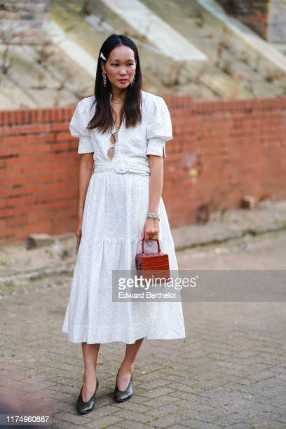 Guest wears a cube rigid crocodile print bag, a ring, a white dress with polka dots, black shoes, long earrings, sunglasses, hair clip, during London...
