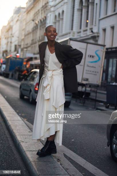 A guest wears a dark blazer white dress and black boots after the Lemaire show during Paris Fashion Week Spring/Summer 2019 on September 26 2018 in...