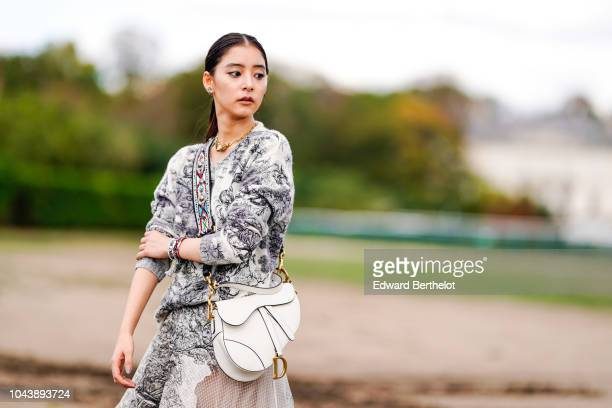 A guest wears a dark blue and white printed wool pullover a white Dior Saddle bag a lace mesh skirt a colored shoulder strap outside Dior during...