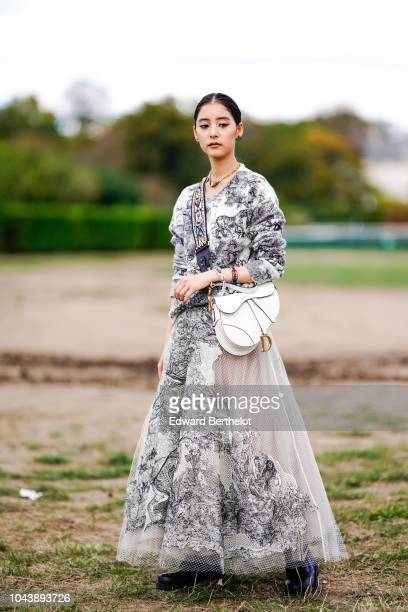 Guest wears a dark blue and white printed wool pullover, a white Dior Saddle bag, a lace mesh skirt, a colored shoulder strap, outside Dior, during...