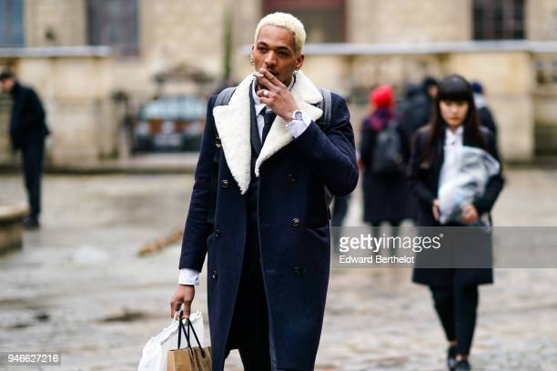 A guest wears a dark blue coat with white sheep wool black pants black shoes outside Thom Browne during Paris Fashion Week Menswear Fall Winter...