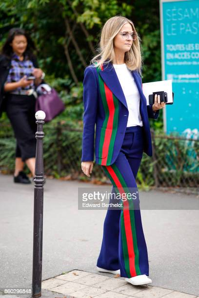 A guest wears a dark blue flare pants pantsuit with red and green stripes white shoes outside Lanvin during Paris Fashion Week Womenswear...