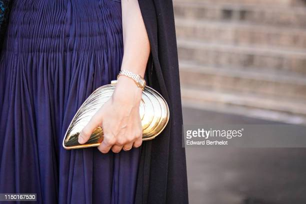A guest wears a dark blue gathered dress a golden musselshaped minaudiere outside the Opera Garnier 350th Anniversary Gala in Paris on May 08 2019 in...