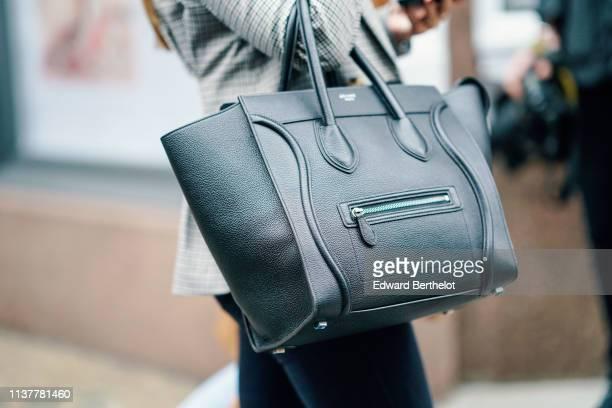 A guest wears a dark blue handbag during London Fashion Week February 2019 on February 16 2019 in London England