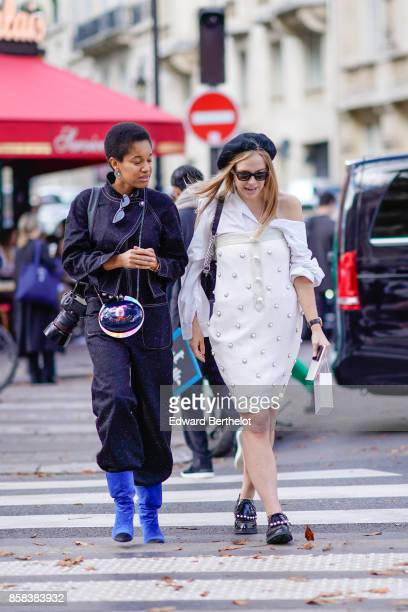 A guest wears a dark blue outfit a glass ball shaped chanel multicolor bag blue boots holds a canon 5d camera with an attached 85mm f12 prime lens a...