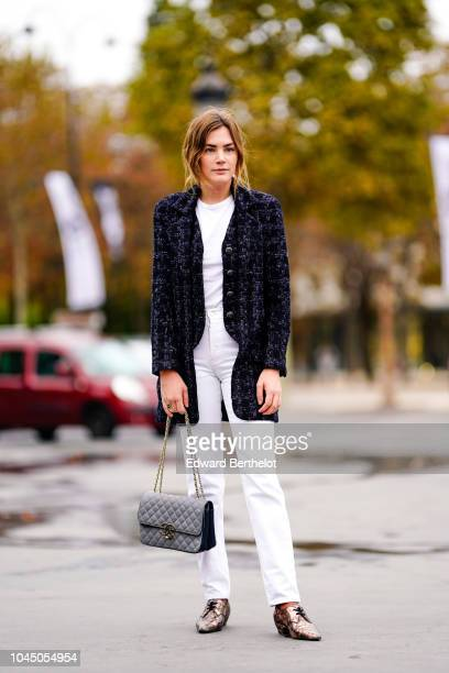 A guest wears a dark blue tweed jacket a gray Chanel bag white pants outside Chanel during Paris Fashion Week Womenswear Spring/Summer 2019 on...