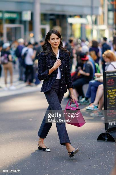 A guest wears a dark blue tweed jacket a pink Hermes bag flared pants silver shoes during London Fashion Week September 2018 on September 17 2018 in...