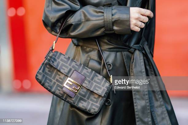 A guest wears a dark brown leather coat a Fendi handbag during London Fashion Week February 2019 on February 15 2019 in London England