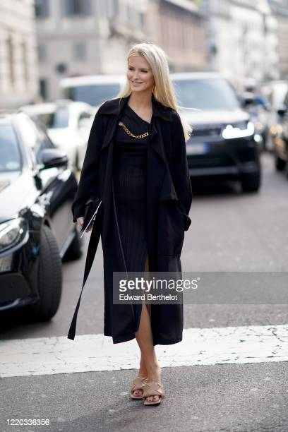 Guest wears a dark long coat, a navy blue dress, a golden chain, brown padded shoes, outside Sportmax, during Milan Fashion Week Fall/Winter...