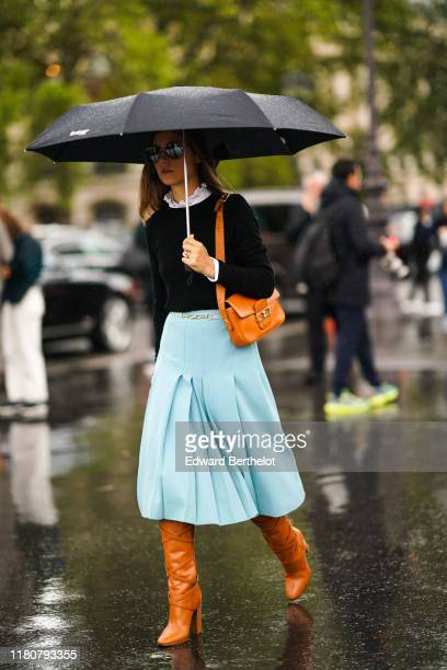 A guest wears a dark pullover a white shirt with ruffled collar a pale blue pleated skirt orange leather boots a brown leather bag holds an umbrella...
