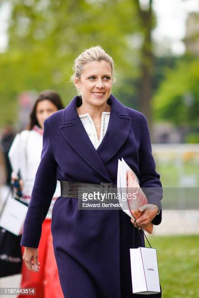 A guest wears a deep purple coat a large brown alligator pattern belt a red Chanel clutch outside the Chanel Cruise Collection 2020 At Grand Palais...