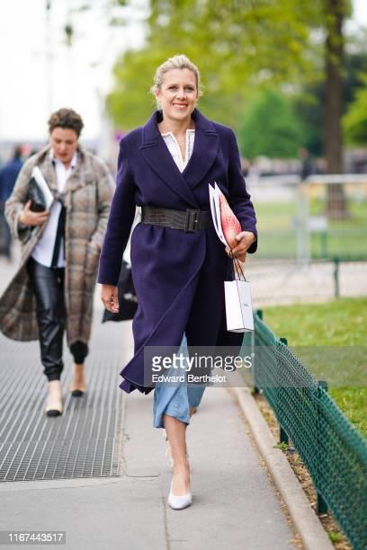 A guest wears a deep purple coat a large brown alligator pattern belt a red Chanel clutch blue denim widelegs crop pants grey pumps outside the...