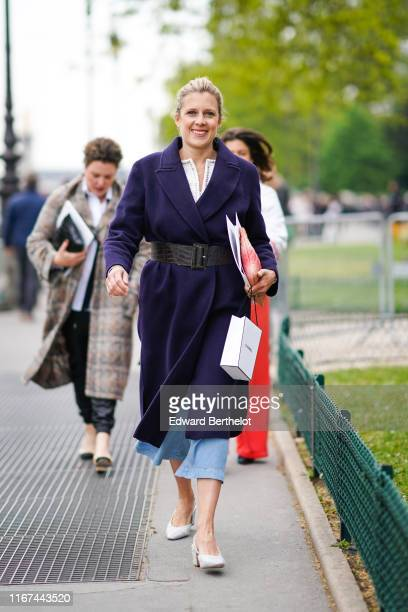 A guest wears a deep purple coat a large brown alligator pattern belt a red Chanel clutch blue denim widelegs crop pants grey leather and tweed...