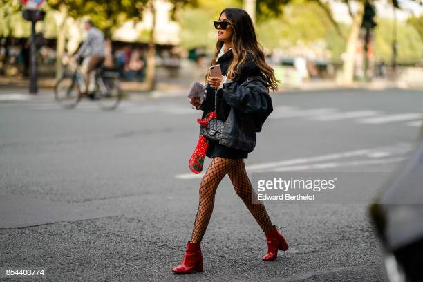 A guest wears a denim jacket fishnet tights red shoes outside Anrealage during Paris Fashion Week Womenswear Spring/Summer 2018 on September 26 2017...