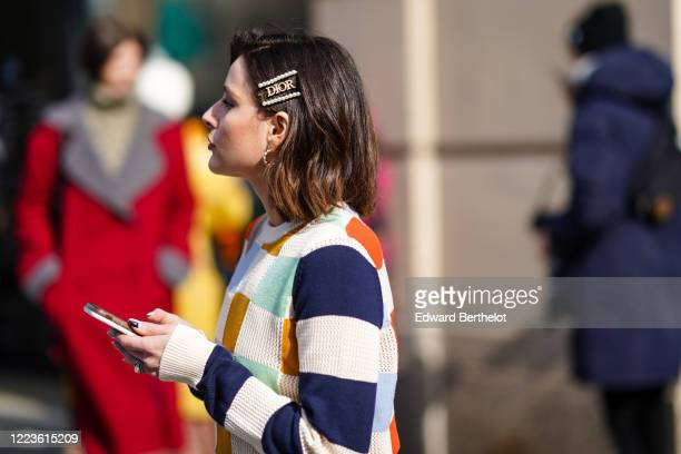 Guest wears a Dior hair brooch, a colored checked wool pullover, earrings, outside Brock Collection, during New York Fashion Week Fall Winter 2020,...